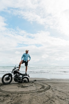 Man stands on a motorcycle by a beach in bail