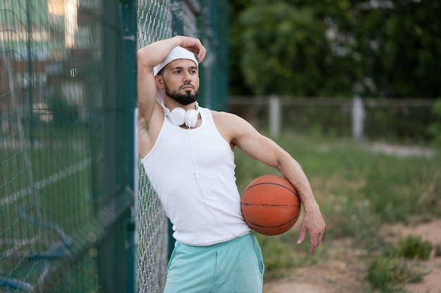 A man stands near a fence on the street, holding a basketball in his hand