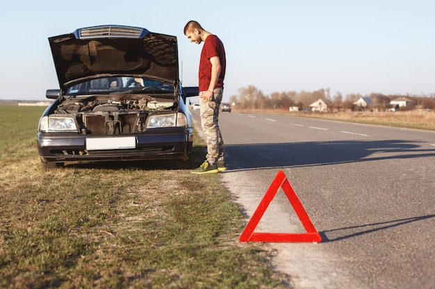 Man stands near his broken car, cant solve problem by himself red triangle as warning sign. man has problems with car