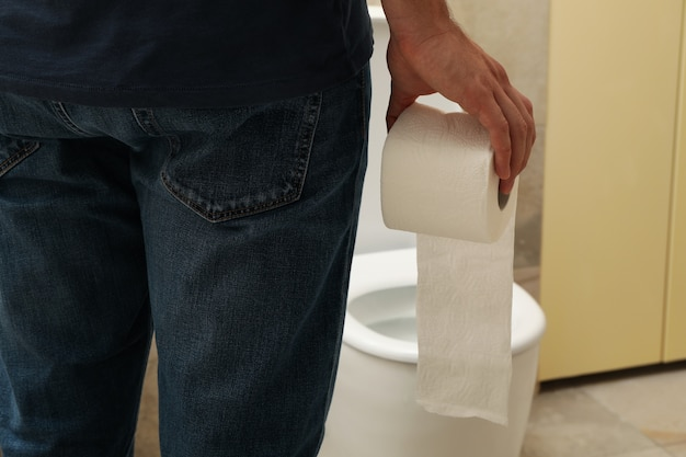 A man stands near the toilet and holds toilet paper