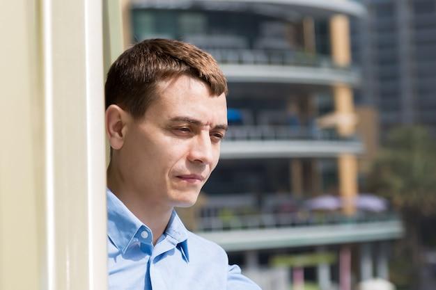 男はバルコニーに立って、都会の生活を見ています。