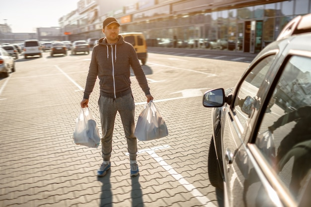 A man stands in parking near a shopping center or a shopping mall.