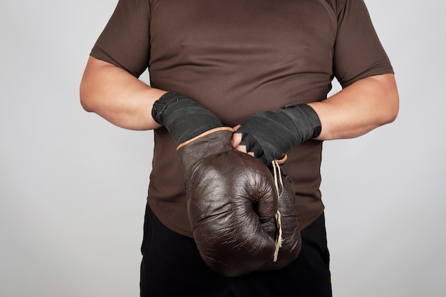 Man stands and puts on his hands very old vintage brown boxing gloves