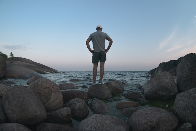 A man stands on the shore of a rocky lagoon. back view