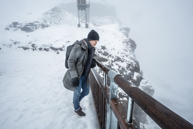 Man stands on a snow cliff in switzerland