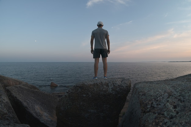 A man stands on a stone cliff near the sea shore. back view