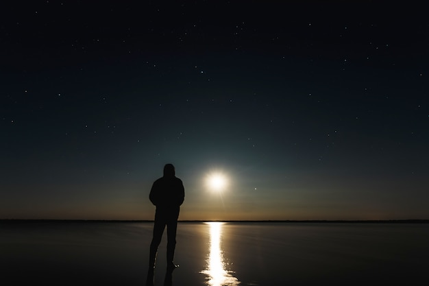 The man stands at the sunset of the moon under the starry sky