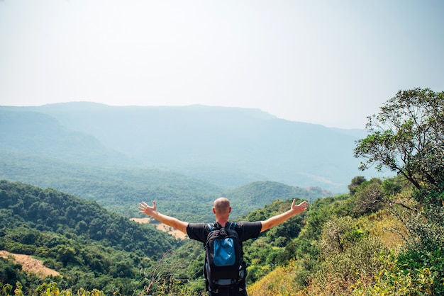 Man stands on top of hill and looks at the mountains covered with forest on sanny day. brutal bald guy with a backpack spread his arms to the sides, view from the back. concept of freedom and travel