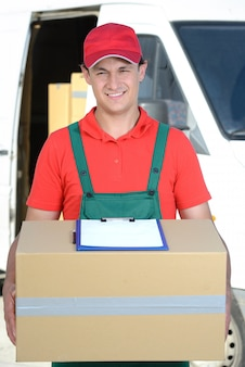 A man stands with a parcel and smiles.