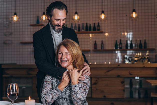 Man stands next to a woman in a restaurant and hugs her from behind