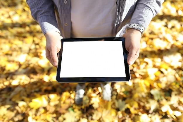 男は彼の手にタブレットで黄色の葉を立っています。