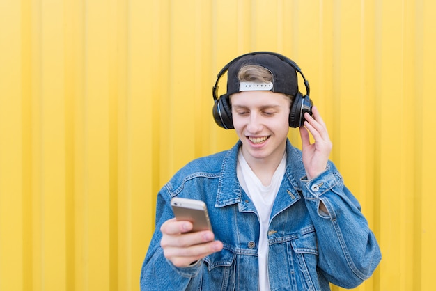 Man stands on a yellow wall listening to music in wireless headphones and switching song