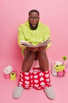 신문을 빤히 쳐다보는 남자는 부끄러운 뉴스가 있는 기사를 읽고 국내 옷을 입고 시력 교정을 위해 큰 투명 안경을 쓰고 화장실 변기에 앉아 있다
