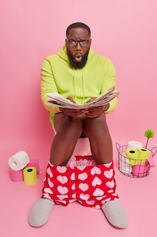 Man stares at newspaper reads article with embarrassing news wears big transparent glasses for vision correction dressed in domestic clothes sits on toilet bowl in restroom