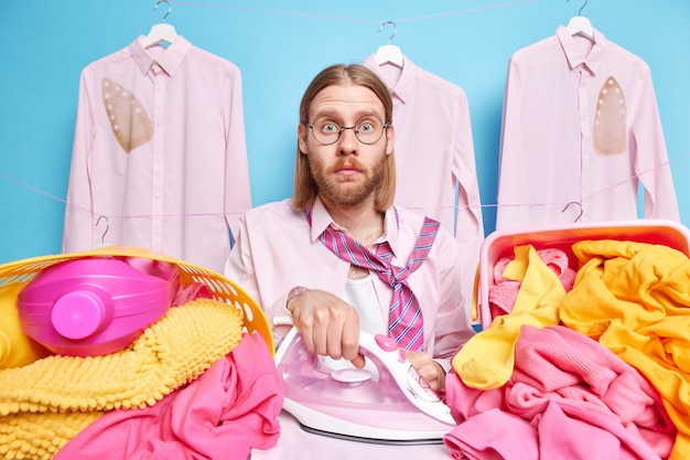 Man stares shocked irons clothes surrounded by stacks of laundry poses on pink