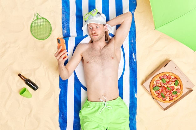 Man stares at smartphone display lies on striped blue towel wears sun hat green shorts sunbathes during day off has recreation outdoor eats pizza drinks beer has lazy time