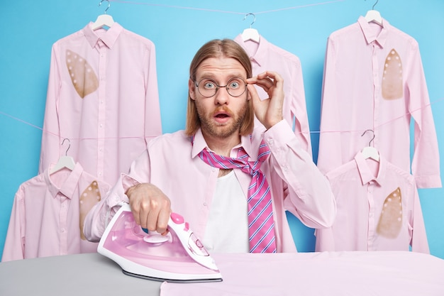 男はs然としたアイロンを見つめる 布は何かを信じることができない 眼鏡を手にしている 洗濯室で青にアイロンをかけた服をぶら下げているポーズ