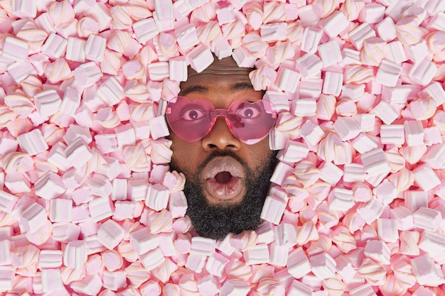 Man stares surprisingly wears trendy heart shaped sunglasses keeps mouth opened from wonder surrounded by marshmallows eats tasty appetizing sweet dessert