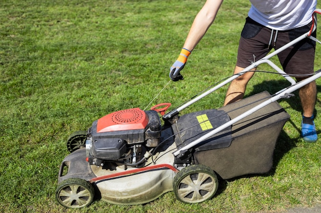 Man starts the engine of a gasoline lawn mower that stands on the grass