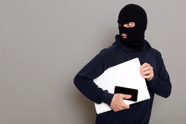Человек крадет ноутбук и телефон