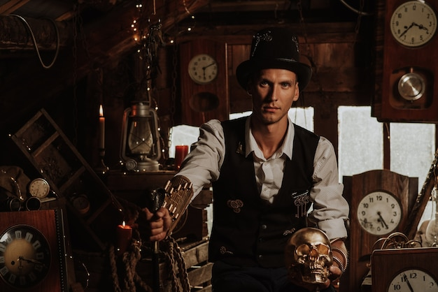 Man in a steampunk suit with a cane and a top hat with a golden skull in his hands in a watch workshop