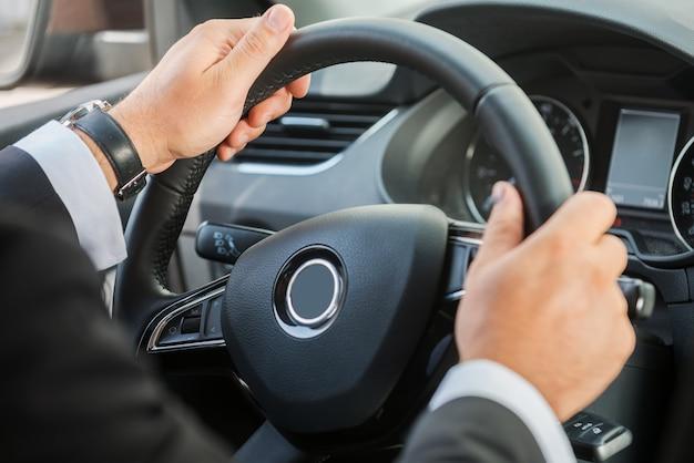 Рулевое колесо человека. крупный план человека в формальной одежде за рулем автомобиля