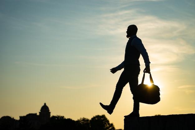 Человек, шагая от края во время заката на фоне неба. понятие риска и выбора.