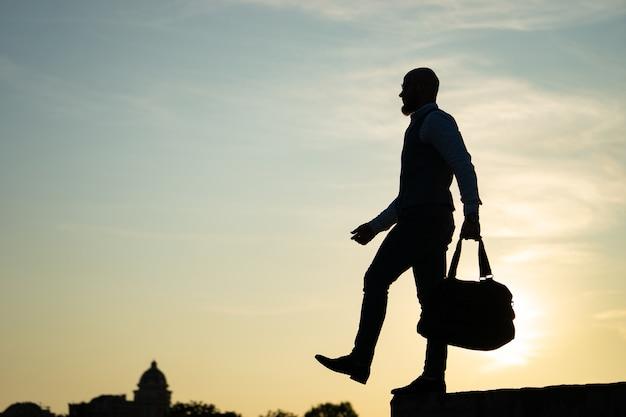 Человек, шагающий с края во время заката в небе. понятие риска и выбора.