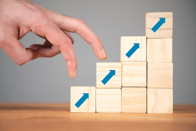 Man stepping her fingers on graphic made of wooden cubes closeup