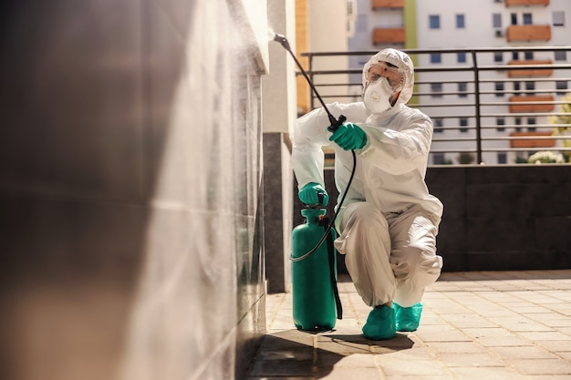 Man in sterile protective uniform crouching and spraying wall with disinfectant in order to prevent corona virus from spreading.