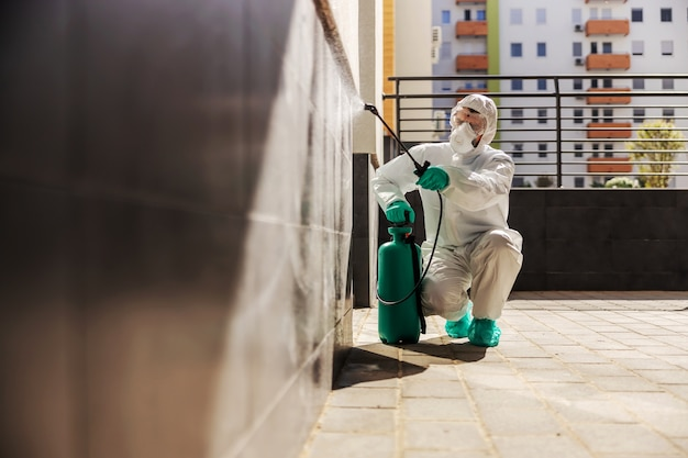 Man in sterile protective uniform crouching and spraying wall with disinfectant in order to prevent corona virus from spreading