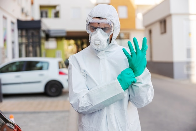 Man in sterile protective uniform standing outdoors and putting rubber gloves