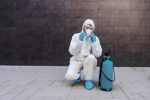 Man in sterile protective uniform with rubber gloves crouching outdoors and putting protective mask on face. next to him is sprayer with disinfectant. prevention form spreading corona virus concept.