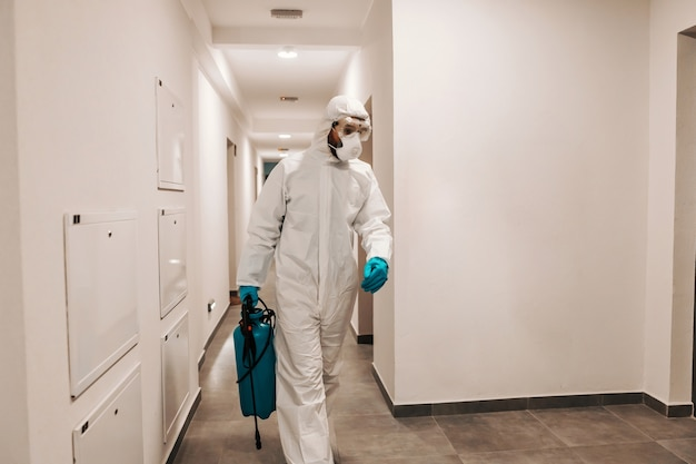 Man in sterile suit disinfecting hall of the building. protection from corona concept.