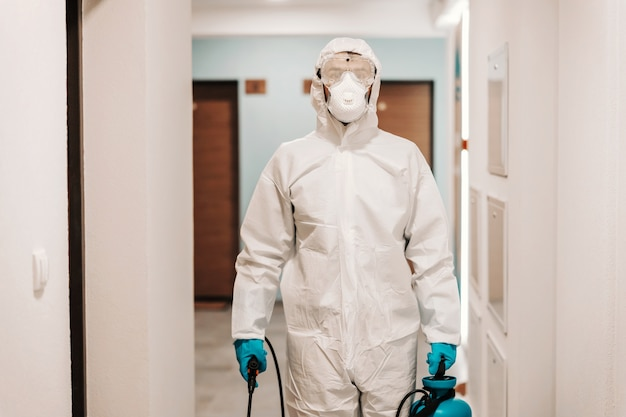 Man in sterile suit disinfecting hall of the building.