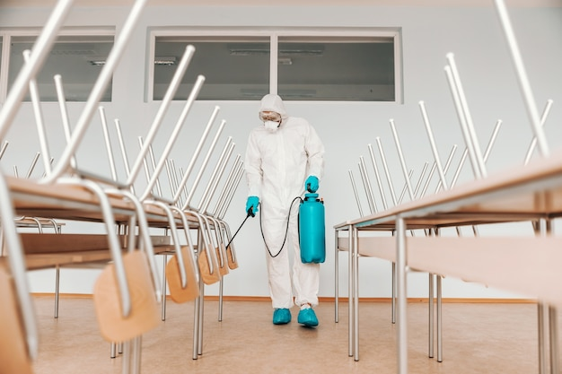 Man in sterile uniform, with gloves and mask holding sprayer and spraying with disinfectant desks and chairs in classroom