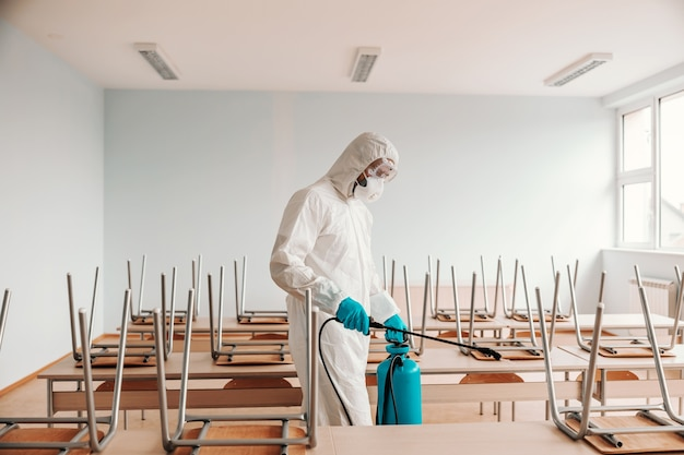 Man in sterile uniform, with gloves and mask holding sprayer and spraying with disinfectant desks