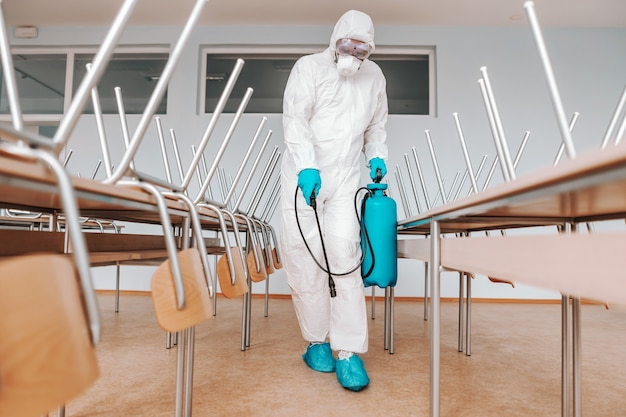 Man in sterile uniform, with gloves and mask holding sprayer and spraying with disinfectant floor in classroom.
