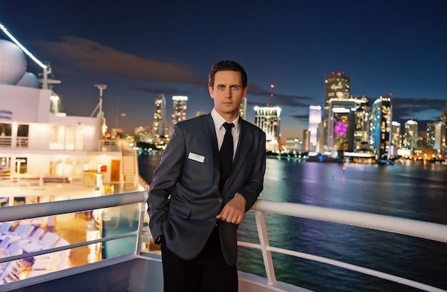 アメリカ、マイアミの夜の船上での男性スチュワード。街のスカイラインのスーツジャケットのマッチョ。水上輸送、輸送。ビジネスのための旅行。放浪癖、冒険、発見、旅。