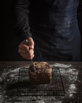 Man sticking a knife in bread high view
