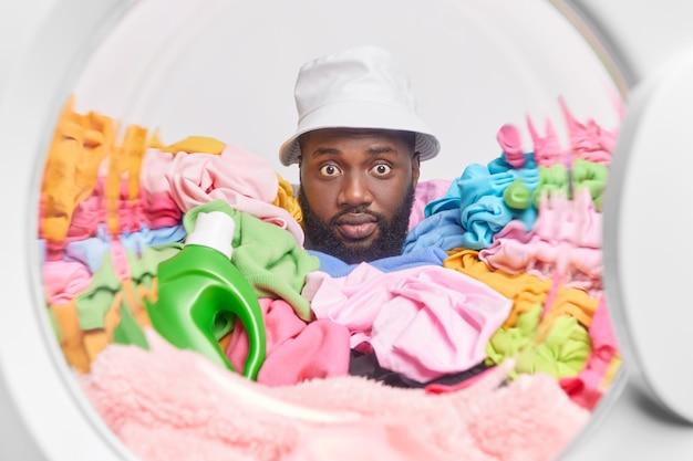 L'uomo attacca la testa nella porta della lavatrice posa intorno alla biancheria colorata con una bottiglia di detersivo indossa panama occupato a fare il lavaggio. lavatrice piena di vestiti sporchi