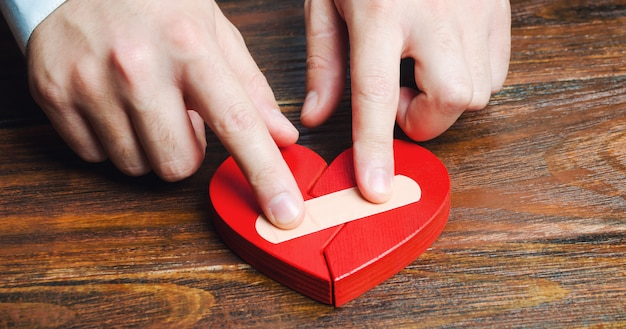 A man sticks together a red heart with a plaster.