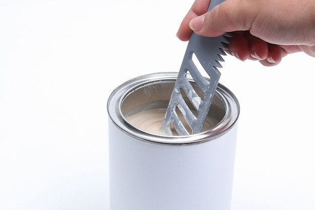 Man stirring white paint in a can on a white background. renovation concept.