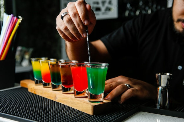 Man stirs the colorful shots green red yellow orange