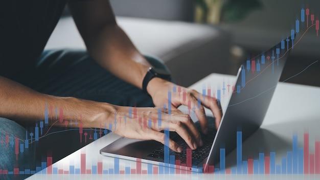 Человек, торгующий акциями дома с помощью компьютера, руки, набирающие текст на клавиатуре ноутбука, двойная экспозиция с графиком фондовой торговли, криптовалюта, концепция анализа фондового рынка.