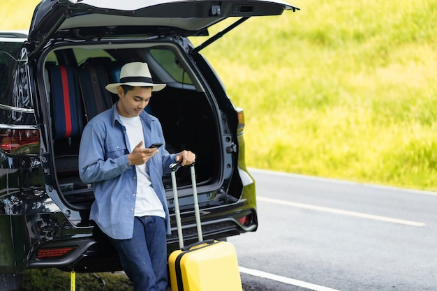 Man stood in the car with his mobile phone and luggage