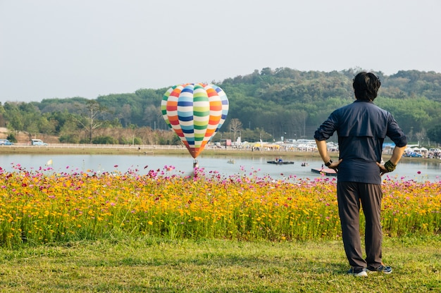 The man stood, turned his back, looked at the balloon, floating above the water with a cosmos flower in front.