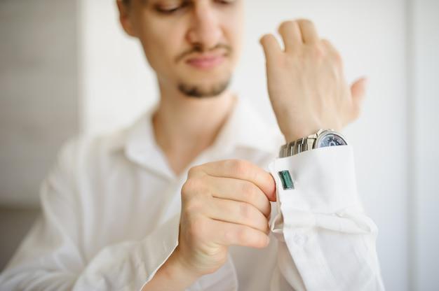 A man straightens cufflinks on a shirt. close-up.