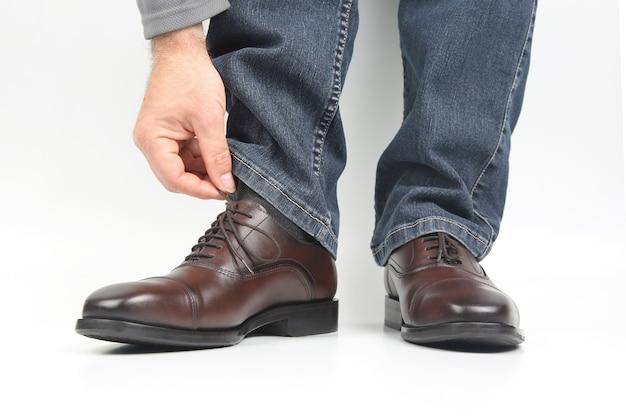 男は白い表面の茶色の古典的な靴で彼の靴紐をまっすぐにします