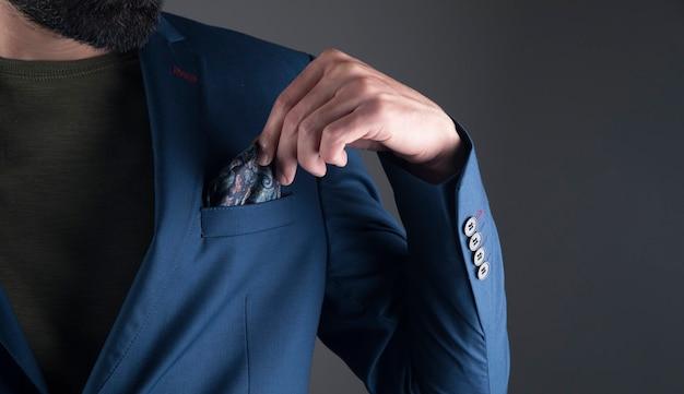 男は灰色のシーンで彼のスーツをまっすぐにします